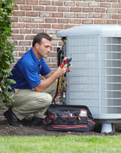 Man repairing a central air conditioner outside a home